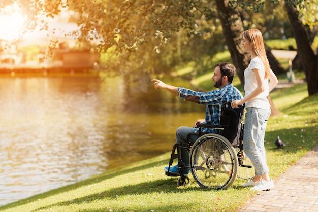 Uma mulher está andando no parque com um homem em uma cadeira de rodas Foto Premium