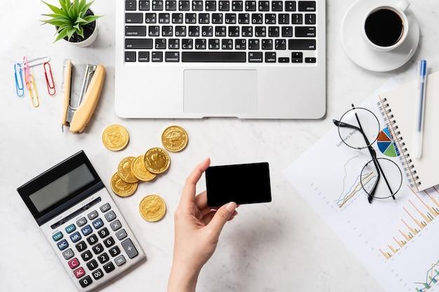 Uma mulher está calculando a taxa, o lucro e fazendo um pagamento online em uma mesa de escritório de mármore moderna, simulação, vista de cima, espaço de cópia, configuração plana Foto Premium