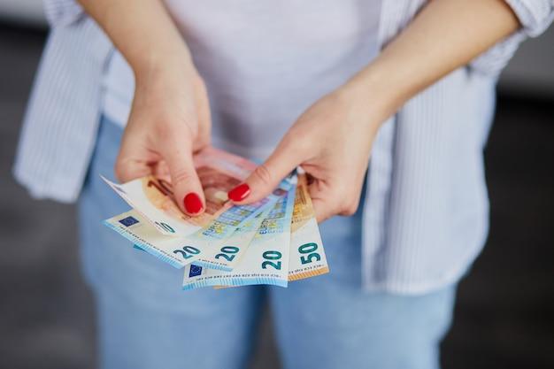 Uma mulher está com dinheiro do euro nas mãos. Foto Premium