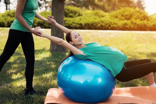 Uma mulher está fazendo exercícios em uma bola azul para yoga Foto Premium