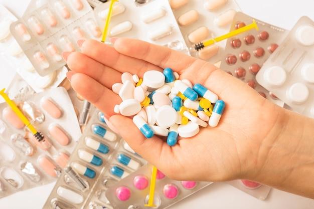 Uma mulher está segurando um monte de pílulas diferentes em sua mão sobre o blister e a seringa Foto gratuita