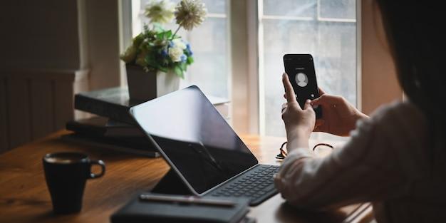 Uma mulher está segurando um telefone celular com uma chamada de um chamador desconhecido. Foto Premium