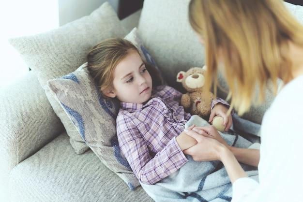 Uma mulher está sentada ao lado de uma menina que está doente Foto Premium
