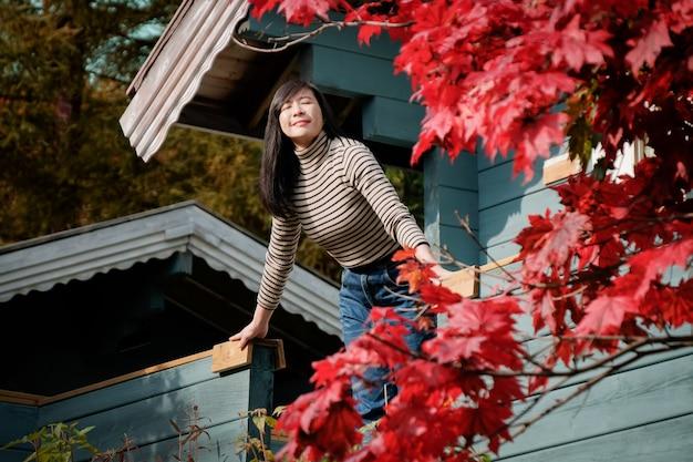 Uma mulher feliz respirando ar fresco no outono, olhos fechados e sorrindo Foto Premium