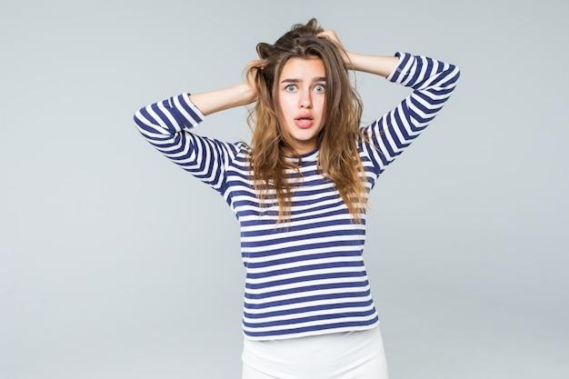 Uma mulher frustrada e irritada está gritando em voz alta e puxando o cabelo dela isolado no fundo branco Foto gratuita