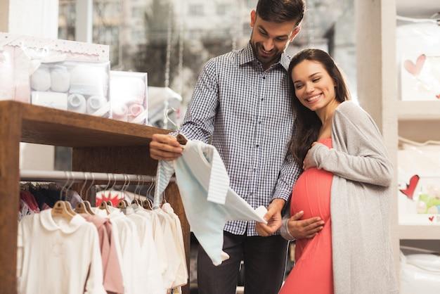 Uma mulher gravida com um homem escolhe bens do bebê. Foto Premium