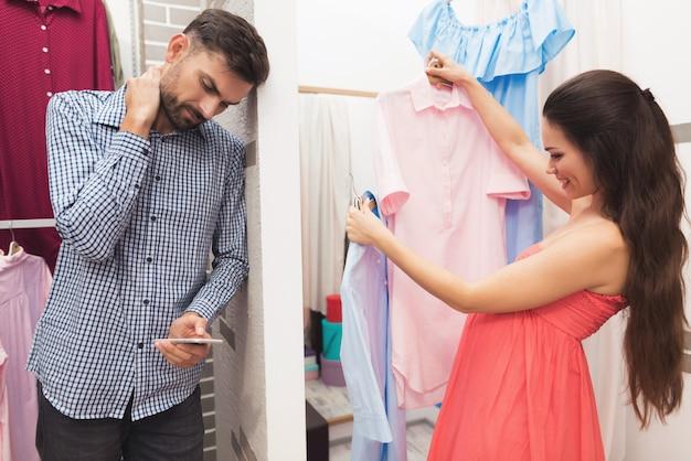 Uma mulher grávida com um homem escolhe roupas na loja. Foto Premium