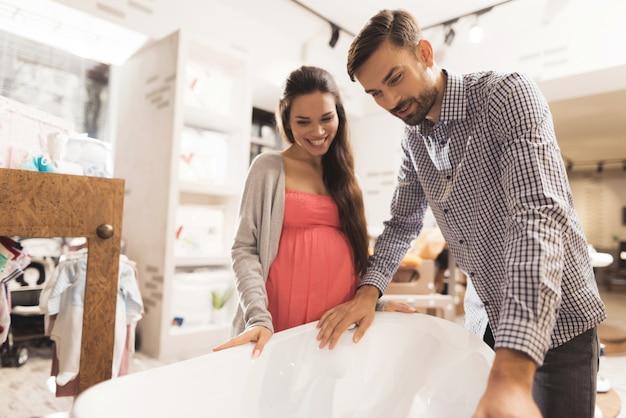 Uma mulher gravida com um homem escolhe um banho do bebê em uma loja. Foto Premium