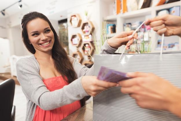 Uma mulher gravida dá o dinheiro a um vendedor em uma loja. Foto Premium