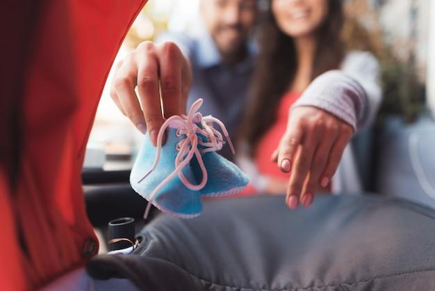 Uma mulher grávida e um homem olham no carrinho de bebê. Foto Premium