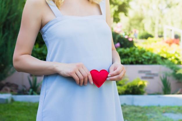 Uma mulher grávida em um vestido azul na natureza. conceito de maternidade gravidez. Foto Premium