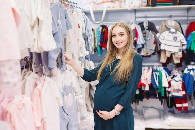 Uma mulher grávida escolhe roupas infantis na loja. Foto Premium
