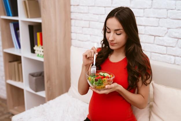 Uma mulher grávida está comendo uma salada. Foto Premium