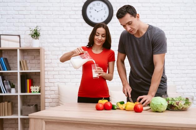Uma mulher grávida está preparando comida com o marido. Foto Premium