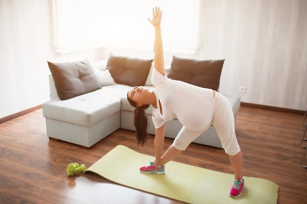 Uma mulher grávida faz exercícios em uma esteira de ioga em casa. gravidez e esportes. oga e pilates para mulheres grávidas. terceiro trimestre de gravidez. Foto Premium