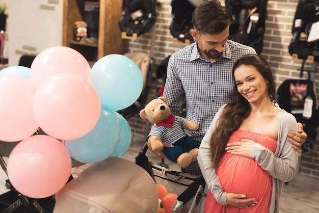 Uma mulher grávida junto com um homem escolher um carrinho de bebê Foto Premium