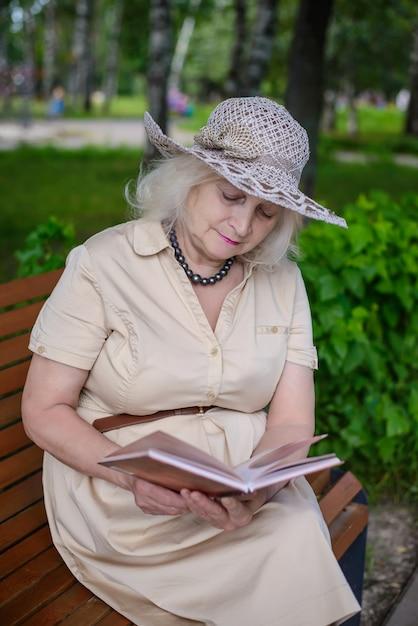 Uma mulher idosa lê um livro no parque Foto Premium