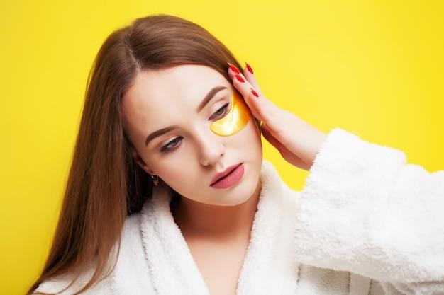 Uma mulher jovem com uma pele bonita aplica adesivos para cuidar da pele sob os olhos Foto Premium