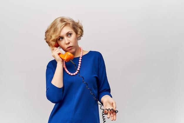 Uma mulher jovem e bonita com cabelo loiro ondulado curto em um vestido azul clássico segura um aparelho retrô do telefone e fala com os clientes com uma expressão de surpresa Foto Premium