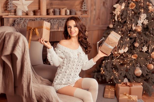 Uma mulher jovem e bonita em um suéter e meias sentado perto de belas árvores de natal e mantendo nas mãos um presentes, interior de casa de ano novo Foto Premium