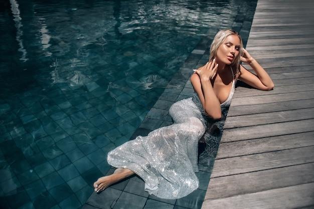 Uma mulher linda de cabelos loiros com os olhos fechados em um vestido longo branco deitado na piscina. Foto Premium