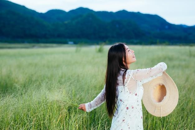 Uma mulher linda e feliz está jogando seu chapéu em um belo prado e há uma montanha no. Foto gratuita