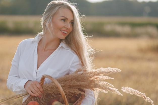 Uma mulher loira e bonita com cabelos longos em um campo ao pôr do sol carrega uma cesta de frutas e um buquê de palha. verão, agricultura, natureza e ar fresco no campo. Foto Premium