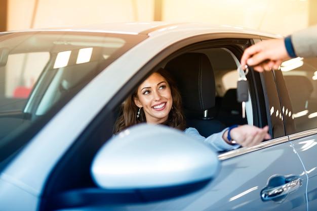 Uma mulher morena atraente sentada em seu carro novo e pegando as chaves de uma concessionária Foto gratuita