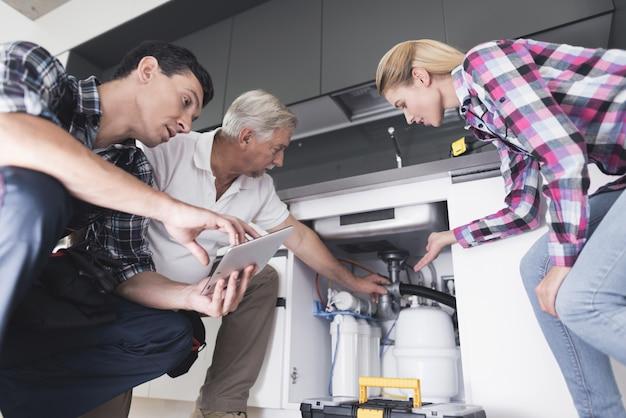 Uma mulher mostra encanadores uma pia da cozinha quebrada Foto Premium