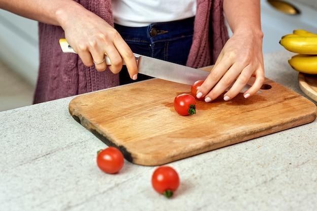 Uma mulher na cozinha cortando tomates para salada Foto gratuita