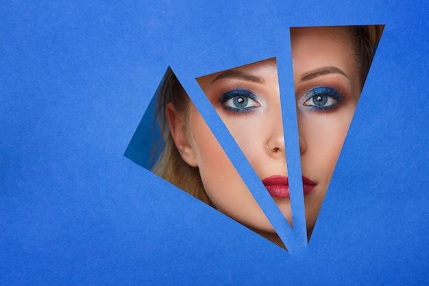 Uma mulher olha no buraco o papel, bela maquiagem. Foto Premium