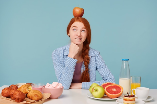Uma mulher pensando em uma alimentação adequada está sentada à mesa Foto gratuita