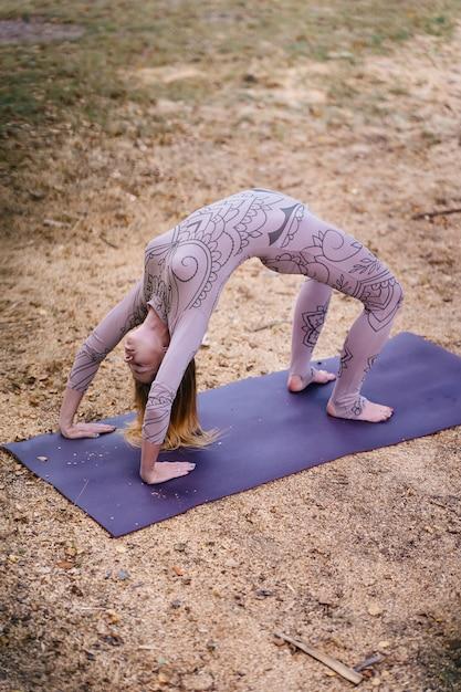 Uma mulher pratica ioga de manhã em um parque ao ar livre. Foto gratuita