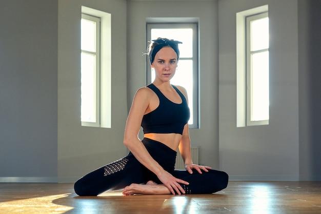 Uma mulher pratica ioga em uma sala de fitness ao amanhecer Foto Premium