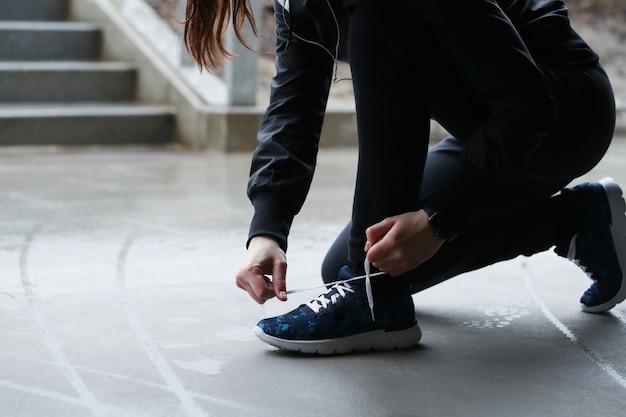 Uma mulher prende os cadarços. pessoa que prende cadarços. Foto gratuita