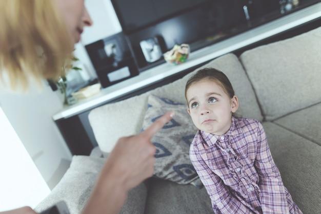 Uma mulher pune uma menina e faz uma careta no dedo Foto Premium
