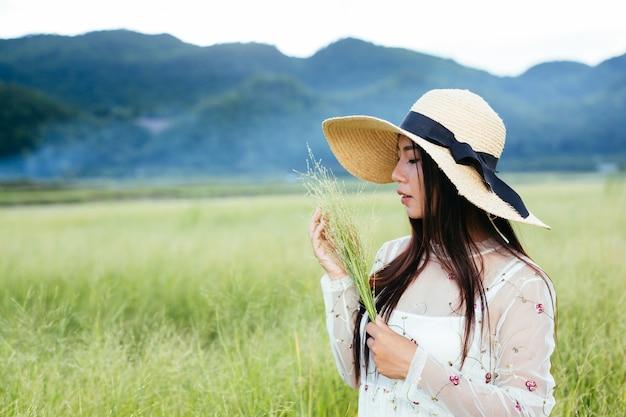 Uma mulher que está segurando uma grama nas mãos em um belo campo de grama com uma montanha. Foto gratuita