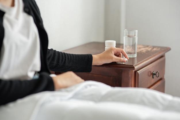 Uma mulher que não está bem no sofá e está prestes a tomar antibióticos. Foto gratuita