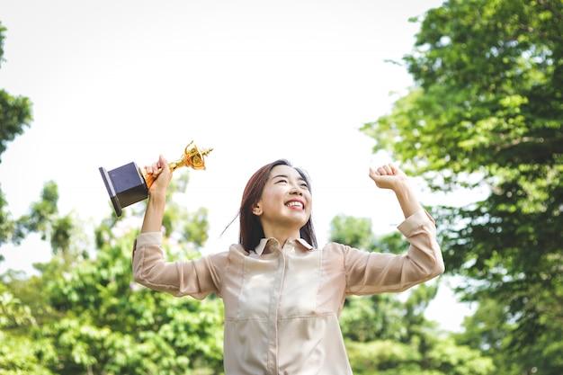 Uma mulher que trabalha em um escritório, segurando um troféu levante as duas mãos, feliz Foto Premium