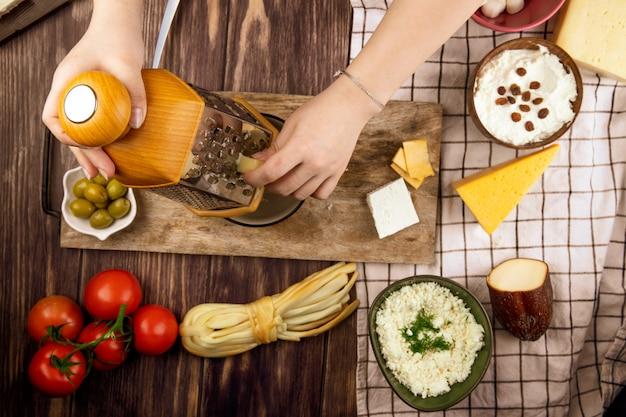 Uma mulher ralar queijo em uma placa de madeira com azeitonas em conserva tomates frescos e vários tipos de queijo na vista superior de madeira Foto gratuita