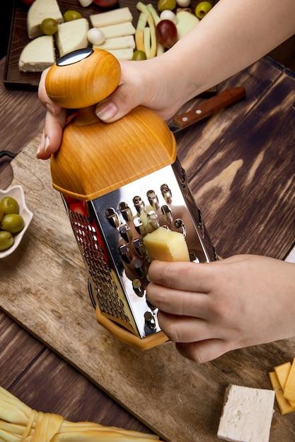 Uma mulher ralar queijo em uma placa de madeira com azeitonas em conserva vista lateral Foto gratuita