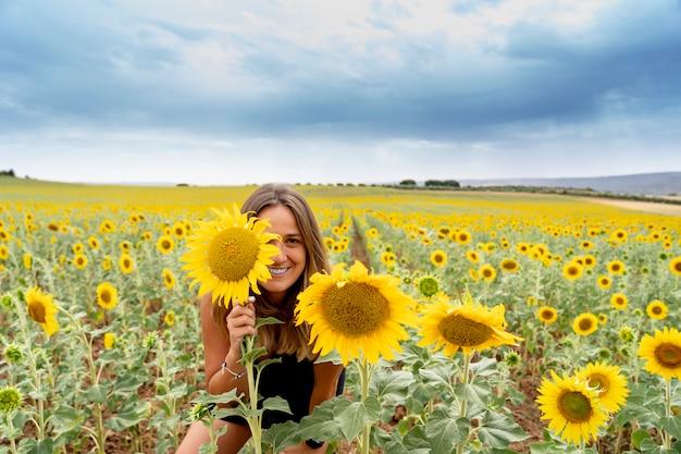 Uma mulher se diverte entre os girassóis. Foto Premium