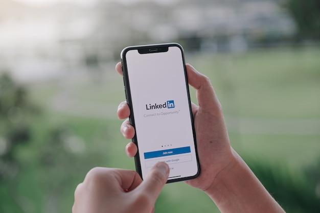 Uma mulher segura smartphone com aplicativo do linkedin na tela Foto Premium