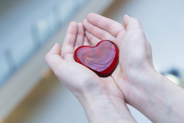 Uma mulher segura um coração de vidro vermelho nas mãos para o dia dos namorados ou doe ajude a dar calor ao amor, cuidar Foto Premium