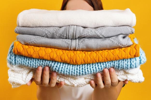 Uma mulher segura uma pilha de roupas de malha quentes Foto Premium