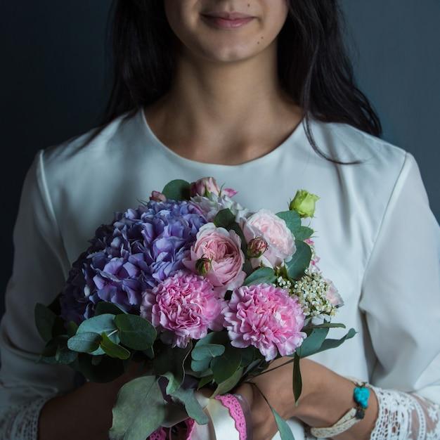Uma mulher segurando um buquê de combinação floral roxa e rosa na mão Foto gratuita