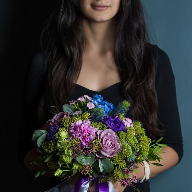 Uma mulher segurando um buquê de flores sazonais na mão Foto gratuita