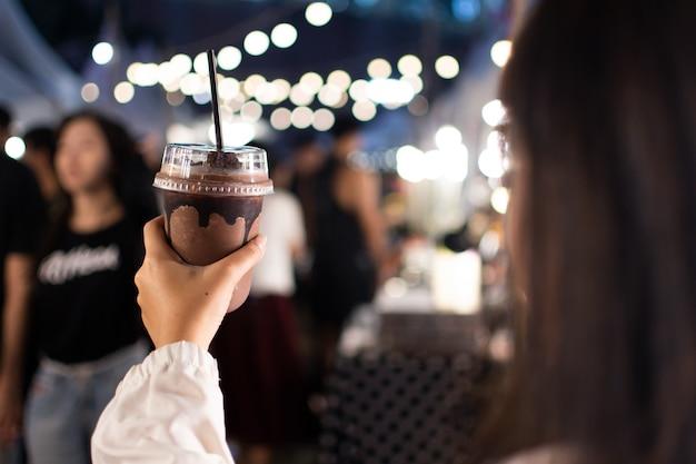 Uma mulher segurando uma xícara de suco de cacau. Foto Premium