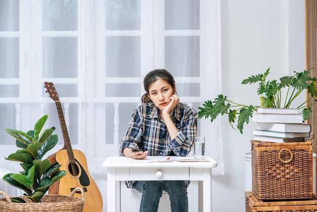 Uma mulher sentada à mesa analisa o documento e está estressada. Foto gratuita