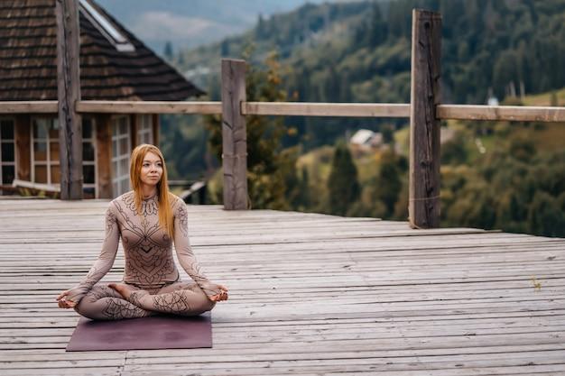 Uma mulher sentada em posição de lótus, de manhã, ao ar livre. Foto gratuita